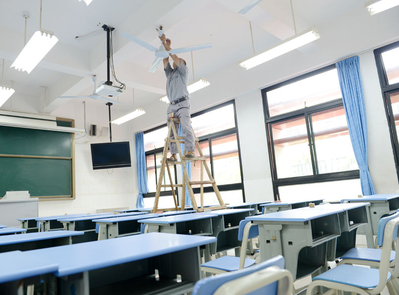 jcpelectric-people repairing the fan in a empty classroom.
